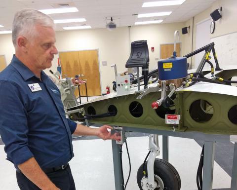 NESCC Aviation Technology program director Richard Blevins demonstrates landing gear simulator